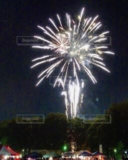 並ぶ夜店と上空に上がる花火の写真・画像素材[3669159]