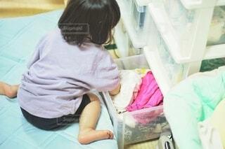 洗濯物を無理やり押し込んでいる子どもの写真・画像素材[3750140]
