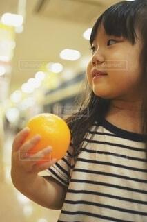 片手にオレンジをもつ女の子。の写真・画像素材[3883096]