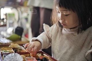 おせち料理を摘まみ食いする女の子。の写真・画像素材[4038677]