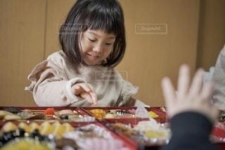 お節を摘まみ食いする女の子。の写真・画像素材[4038673]
