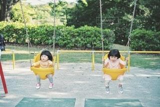 公園のブランコで遊ぶ姉妹の写真・画像素材[4448763]