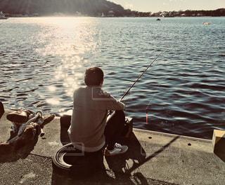 水の体の横にドックに座っている男の写真・画像素材[987831]