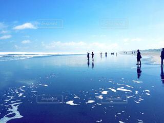 水の体の横に立っている人のグループの写真・画像素材[1385097]