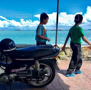 男性と女性のビーチに、バイクに座っての写真・画像素材[1385388]