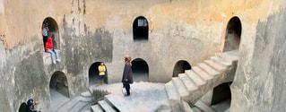 石造りの建物の前に座っている人の写真・画像素材[1815396]