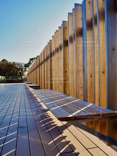 フェンスの前にある木製のドックの写真・画像素材[2890751]