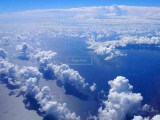 飛行機から見た白い雲と青い海の写真・画像素材[2423309]