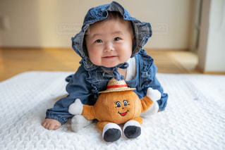赤ん坊を抱いている小さな男の子の写真・画像素材[2415407]