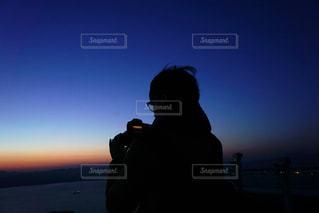 夕焼けの前に立っている男の写真・画像素材[2513526]
