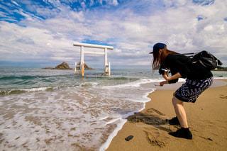 砂浜で波に後ずさりする女性の写真・画像素材[2514154]
