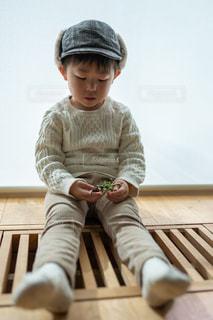 木製のベンチに座っている赤ん坊の写真・画像素材[2685874]