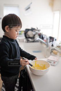 少年がボウルで食べ物を準備しているの写真・画像素材[2686319]