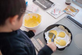 食べ物の皿を持ってテーブルに座っている人の写真・画像素材[2686357]