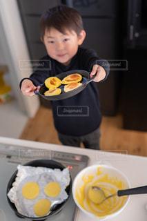 食べ物の皿を持ってテーブルに座っている少年の写真・画像素材[2686378]
