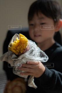 サツマイモを食べようとする少年の写真・画像素材[2691683]