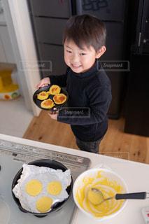 食べ物のあるテーブルに座っている小さな男の子の写真・画像素材[2698353]