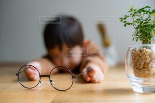 メガネを持って寝転んでる男の子の写真・画像素材[2768895]