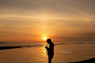 夕日を背景にビーチに立つ男の写真・画像素材[2858226]