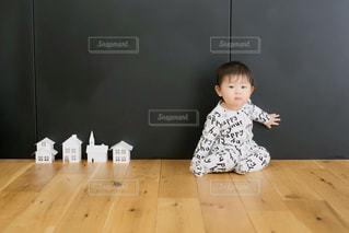 木製の床に座っている小さな女の子の写真・画像素材[2870095]