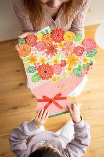 子供が母親にフラワーブーケ式紙を手渡している場面の写真・画像素材[2884770]