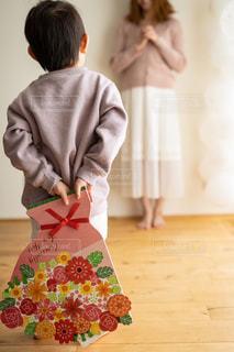 子供が母親にフラワーブーケ色紙を渡そうとしている場面の写真・画像素材[2884768]