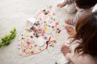 子供と母親がフラワーブーケ色紙を眺めている場面の写真・画像素材[2886145]