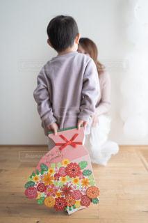 子供が母親にフラワーブーケ色紙を渡そうとしている場面の写真・画像素材[2896349]