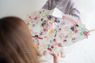 子供が母親にフラワーブーケ色紙を手渡す場面の写真・画像素材[2896351]