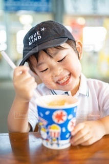 コーヒーを飲みながらテーブルに座っている小さな男の子の写真・画像素材[3605945]