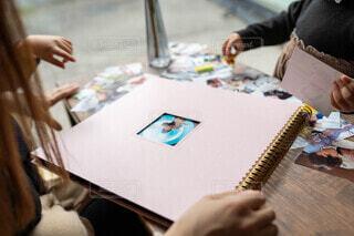 テーブルの上にケーキを持ってまな板の上に座っている女性の写真・画像素材[3843894]