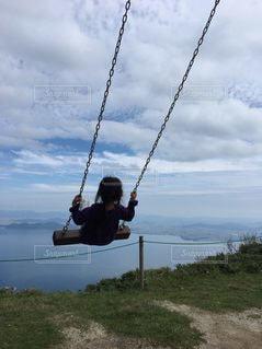 空の中でブランコに乗る女の子の写真・画像素材[2414163]