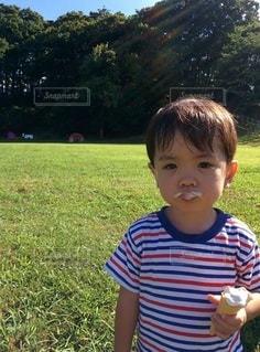 草の上に立っている小さな男の子の写真・画像素材[2414176]