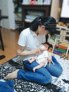 おばあちゃんに抱かれてミルクを飲む赤ちゃんの写真・画像素材[2435625]