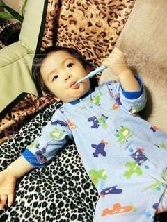 寝転んで歯を磨く小さな男の子の写真・画像素材[2437834]
