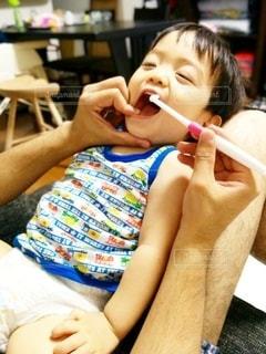 仕上げ歯磨きしてもらう小さな男の子の写真・画像素材[2437833]