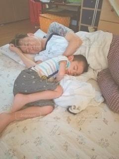 おじいちゃんの横で寝る小さな男の子の写真・画像素材[2440099]