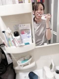 鏡の前で歯を磨く女性の写真・画像素材[2440140]