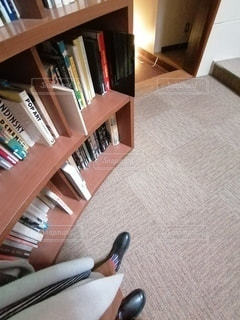書棚とロングカーディガンと黒いブーツの写真・画像素材[2762412]