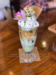 木製のテーブルの上に座っている花でいっぱいの花瓶の写真・画像素材[2415090]
