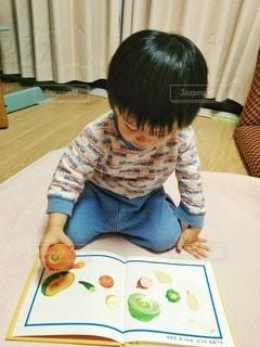 人参を本と見比べる2歳児の写真・画像素材[2856581]