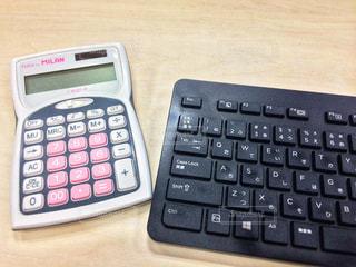 卓上のキーボードと電卓の写真・画像素材[2418930]