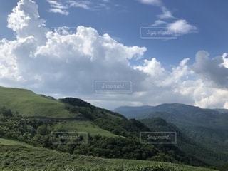 山を背景にした大きな緑の野原の写真・画像素材[2431148]