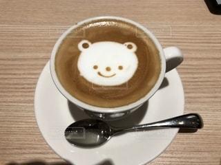 コーヒー1杯の隣にある木製のテーブルの上のスプーンの写真・画像素材[2795105]