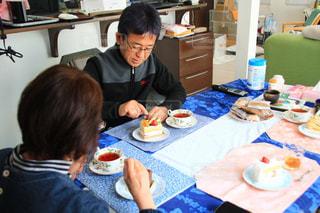バースデーケーキを持ってテーブルに座っている人々のグループの写真・画像素材[3105014]