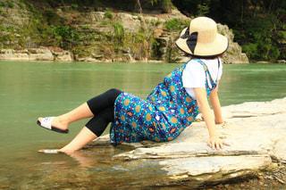 水の体の隣に座っている人の写真・画像素材[3454499]