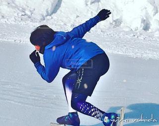 雪に覆われた斜面をスノーボードに乗っている男の写真・画像素材[2494979]