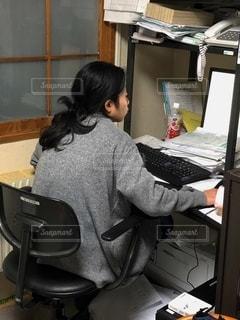 ラップトップコンピュータの前の机に座っている人の写真・画像素材[2726699]