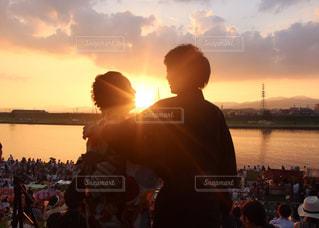 夕焼けの前に立つ人々のグループの写真・画像素材[2457198]