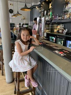 テーブルの上に座っている小さな女の子の写真・画像素材[2421981]